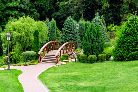 Landscaping of a park in the backyard with a footpath for walks through the wooden decorative bridge to bushes and trees on summer day.