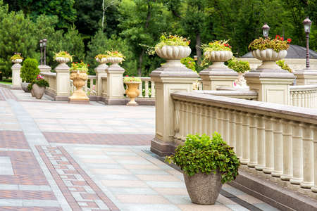 the back yard of a residential building with paving slabs and stone flowerpots on the walkway and on the railing pedestals with balustrades, stone flowerpots with flowers and green trees in the background. Reklamní fotografie