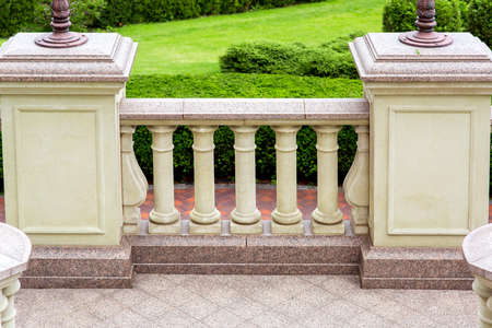 a balcony with stone pedestals and railings with balustrades on the floor a granite square tile in the background a backyard with bushes and green grass. Archivio Fotografico