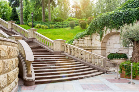 granite staircase with stone railings and balustrades with a wall rustic design in the background landscape with plants from bushes and trees and sunny glare.