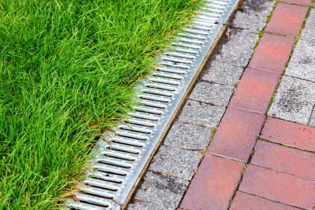 An iron gutter with grate to the drainage system on the side of the footpath with green lawn, close up.