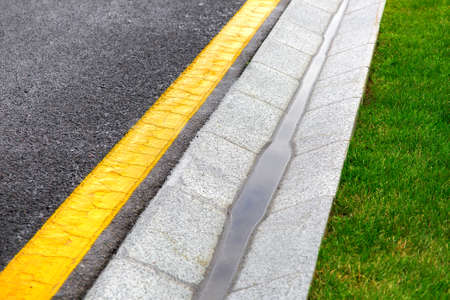 drainage system edge tray with stream rain water near an asphalt road with a yellow marking and a green lawn after rain. Reklamní fotografie