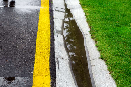 the current rainwater in the filled canal is a cement ditch of the drainage system on the side of a wet asphalt road after rain, background on the topic of environmental safety. Foto de archivo