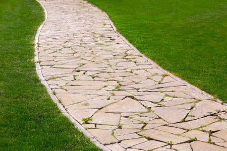 footpath from different pieces of stone paved with a pattern in a park with a curb and a green lawn.