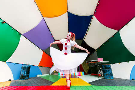 a girl in a white dress and a make-up clown on her face with red hair is standing on the street stage decorated with different bright colors, the image of a woman on the theme of Halloween.