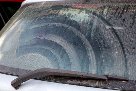 dirty car back window covered mud with dust, close up.