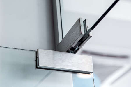 glass door hinges, close up of hinged accessories of transparent partitions. Reklamní fotografie