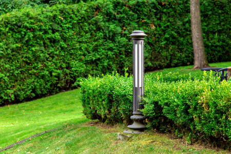 Iron lantern mounted on the ground in a park with green deciduous bushes and green grass growing on a slope on a summer day.