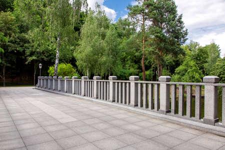 Vista de un puente con baldosas de piedra y barandas de granito con columnas cuadradas en el fondo de un parque con árboles verdes y cielo, nadie. Foto de archivo
