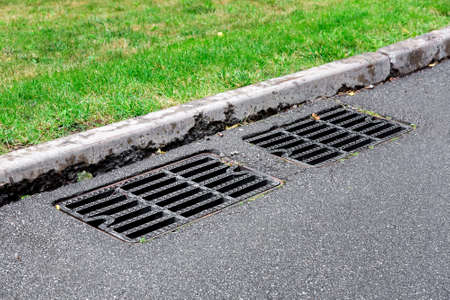 drainage system of an asphalt road with a black manhole grill for sewage near the border on sunny summer day.