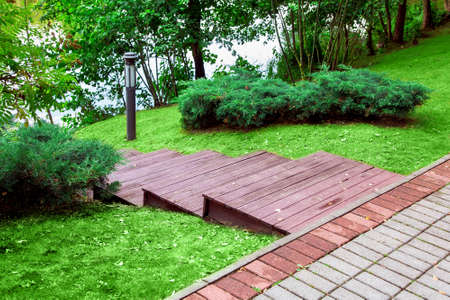 wooden staircase with stairs downhill to the river, landscape design lawn with bushes and ground lamp.