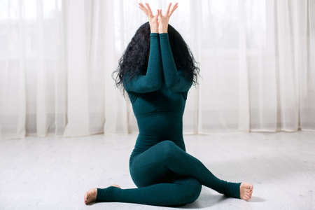 sports trainer girl with black hair and a green tracksuit sits on the floor with her legs crossed and arms raised up, covering her face with them, front view. Stok Fotoğraf