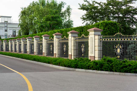 a stone fence with a rustik and an iron forged insert with a pattern and peaks near asphalt road along the fence.