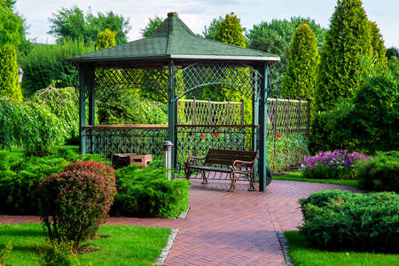an iron gazebo with a roof and a park bench with green plants, bushes and trees on a summer day.