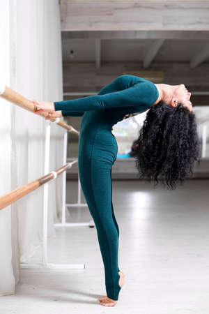sportswoman in tracksuit stands on toes and holds hands on the railing in the gym.