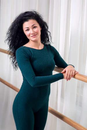 young happy brunette girl with curly hair in green sportswear is standing at the railing posing and looking at the camera, on a background of white curtains. Zdjęcie Seryjne
