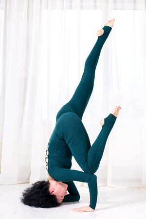 the girl on sportswear is engaged in yoga and stands in a pose of a asana upside down on a white floor in the room. Foto de archivo