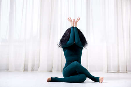 a sports trainer girl with black hair and a green sporstwear sits on the floor with her legs crossed and arms raised up, covering her face with them, front view with copy space.