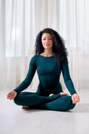 a brunette curly hair girl on green sportswear for yoga is sitting in a lotus position in a bright room.