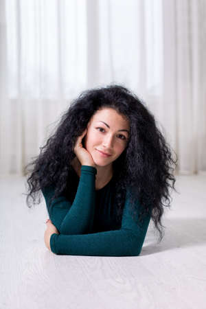 brunette portrait of a young happy girl with black curly hair who lies on the floor and holds her head with her hand, in a light interior and dark green tracksuit.