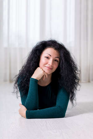 a portrait of a young happy girl with black curly brunette hair who lies on the white floor and holds her head with her hand, in a light interior and dark green pullover.