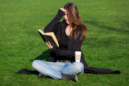 a brunette girl sits in a green meadow and indignantly reads a hardback book holding it in her left hand, and her right hand in her forehead from discontent and misunderstanding of the contents.