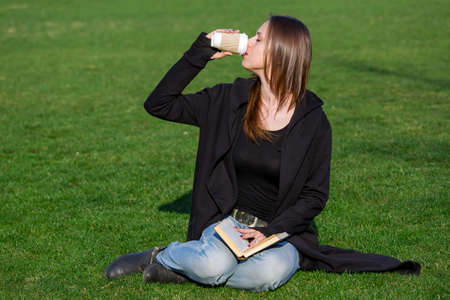 a young brunette with long hair in a black coat and blue jeans sits on a lawn in a park with a book on her lap and drinks hot coffee from a disposable paper stack on sunny day.