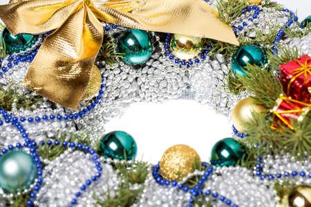 Objeto de decoración navideña de conos grises decorados con juguetes navideños y abalorios con un lazo dorado con espacio de copia libre para un texto de felicitación.