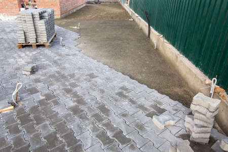 the process of building a sidewalk from stone tiles with a sidewalk and a pallet of new tiles.