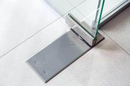 Glass door fittings, swivel mechanism holding the door metal loop close up. Reklamní fotografie