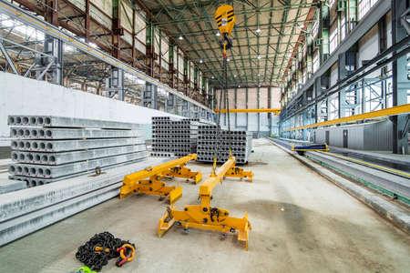 overhead crane beam hoist concrete slab on a plant for the production of hollow floor slabs, industrial background theme nobody. Reklamní fotografie