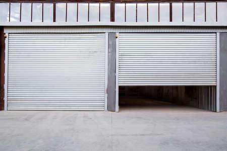 Contraventana de hierro gris de un edificio industrial con porche de hormigón gris.
