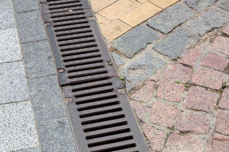 Rejilla de drenaje de un sistema de tormentas en una acera peatonal de baldosas de piedra, de cerca.