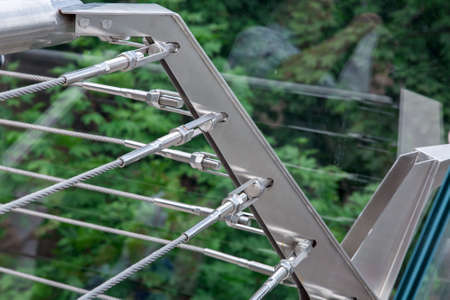 a corner of a glass bridge with tension steel cables and a cable tensioner with thread over green trees.