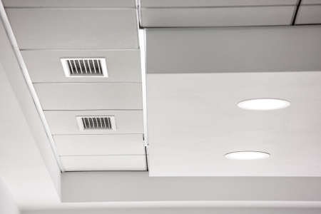 multi-level ceiling with three-dimensional protrusions and a suspended tiled ceiling with a built-in round led light and a ventilation grille. 版權商用圖片 - 137740466