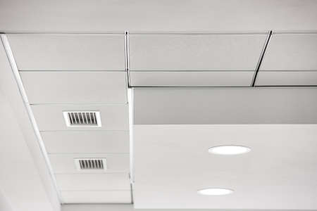 multi-level gypsum plasterboard ceiling and a white square tile suspended ceiling with integrated lighting lamps and ventilation grilles. 版權商用圖片 - 137740325