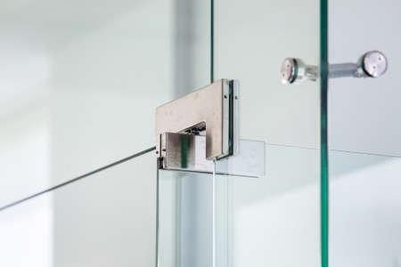 Żelazne zawiasy drzwi szklanych na styku narożnym konstrukcji szklanej, z bliska. Zdjęcie Seryjne