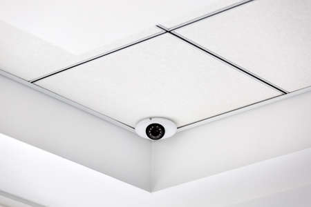CCTV camera in the corner on a white suspended ceiling, security system close up.