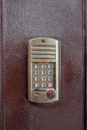 an intercom with a microphone and speaker for ringing an apartment with a keypad for dialing and a scanner key chip for access on iron doors, close up nobody.
