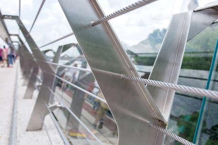 Puente de vidrio con cables de tensión de acero y soportes de barandilla de acero.
