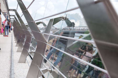 glass bridge with tension steel cables and steel railing supports with reflection on glass. 免版税图像