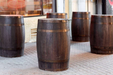 brown wooden wine barrel on the street on stone paving slabs, bar restaurant decorations close up nobody.