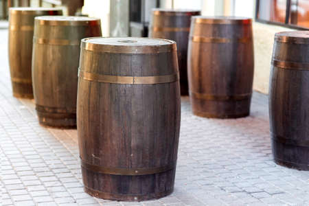 brown wooden barrel on the city street on stone tile, row of cask decorations close up nobody.