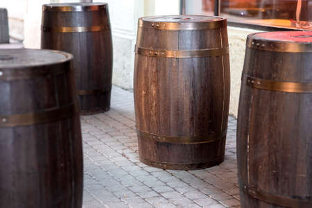brown wooden rum barrel on the street on stone paving slabs, bar restaurant decorations close up nobody. Stock fotó