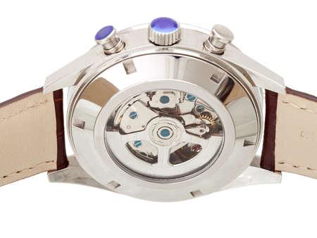 mécanisme interne de la montre-bracelet avec engrenages derrière le couvercle en verre du boîtier en fer, gros plan.