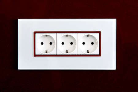 socket with plugs for standard type F plug in white plastic case on a burgundy glossy stone wall.