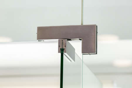 glass door hinges to office, close up of hinged accessories of transparent partitions.