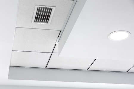 multi-level ceiling with three-dimensional protrusions and a suspended tiled ceiling with a built-in round led light and grille ventilation system, close up details.