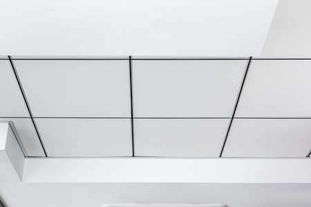 multi-level ceiling with three-dimensional protrusions and a suspended tiled ceiling white color, close up unlabel details.