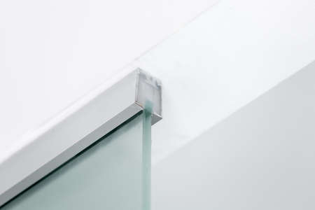 metal fastening to the ceiling of a glass partition, closeup of interior details.